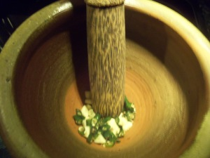 Chopped garlic and chili peppers in mortar with pestle
